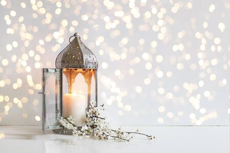 White flowers, prunus tree blossoms and glowing silver decorative Moroccan lantern on table background with golden bokeh lights. Iftar dinner. Ramadan Kareem greeting card, invitation.