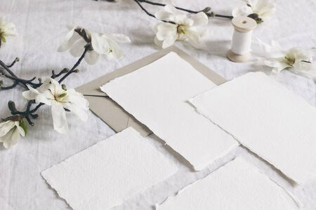 Wedding stationery set. Mock-up scene with blank paper greeting cards, envelope on linen tablecloth background with white magnolia stellata tree branches and ribbon. Feminine still life.