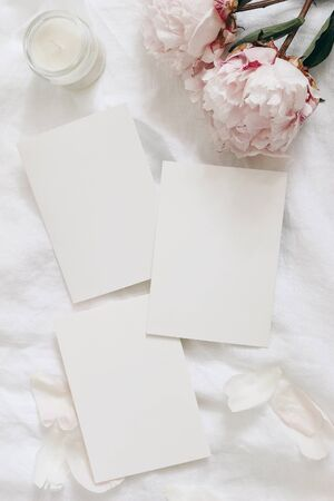 Wedding stationery, still life composition. Greeting cards mockup scene. Blank sheets of paper and pink peony flowers on white linen table cloth. Vintage feminine styled photo, flat lay, top view, 免版税图像