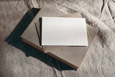 Moody stationery still life scene. Old book, blank sheet of paper, greeting card mockup and envelope in sunlight. Beige linen tablecloth background. Harsh long shadows. Rustic high angle view. 免版税图像