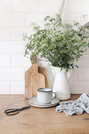 Rustic kitchen interior. Still life composition with cup of coffee, wooden chopping boards and cow parsley bouquet in jug. White brick wall, metro tiles. Scandinavian design, home staging, concept 免版税图像