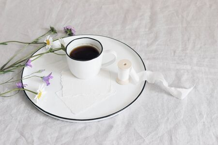 Spring, summer still life scene. Blank cotton paper greeting cards mockups on ceramic plate. Cup of coffee, silk ribbon, daisies and bluebells flowers on linen table cloth, floral composition, top