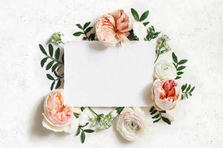 Feminine wedding, birthday mock-up. Blank paper greeting card. Floral frame of white and pink ranunculus, carnation and astrantia flowers. Lentisk leaves, concrete table background. Flat lay, top view.