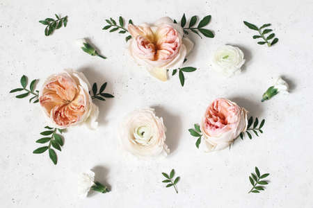 Floral composition with pink English roses, ranunculus and green leaves on white concrete table background. Flower pattern. Flat lay, top view. Wedding or birthday styled stock photo.