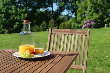 Bottle and glass of orange juice on wooden table with chair. Blurred green trees and hill tops background. Outdoor breakfast with fruit in countryside. Picnic or garden party snack. No people.