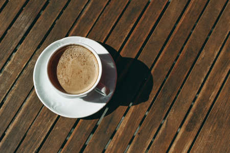 White cup of cappucino coffee in sunlight with harsh shadows on old wooden table background. Breakfast, break concept. Flat lay, top vie. No people, minimal composition.