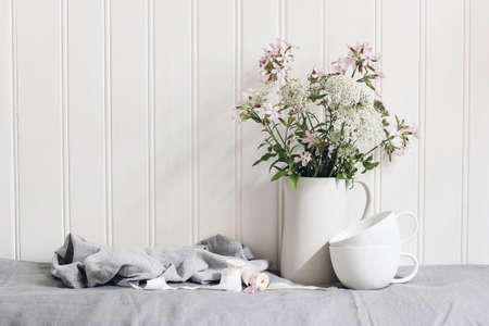 Bouquet of pink soapwort and wild carrot flowers in ceramic pitcher. Empty coffee cups on linen table cloth. White wooden wall background. Feminine wedding table, interior composition. No people.