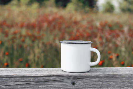 Close up of metal mug on old wooden table, board with defocused blooming mountain meadow. Outdoor tea, coffee time. Mockup of white enamel cup. Lifestyle relax, trekking and camping concept.