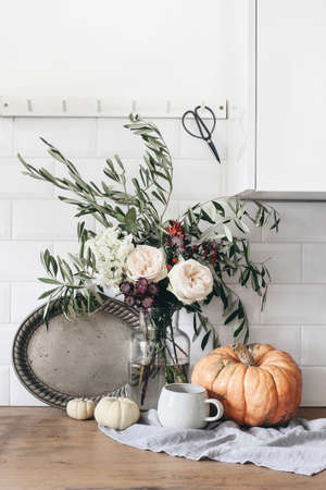 Autumn still life composition. Cup of coffee, vintage silver tray and floral bouquet. Fall kitchen still life with pumpkins. Wooden table background. Thanksgiving, Halloween concept. Interior design.