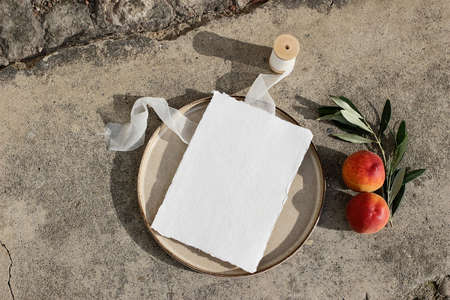 Summer wedding stationery. Blank greeting card mockup on ceramic plate in sunlight. Silk ribbon, peach fruit and olive branch on concrete background. Feminine flat lay, top view, no people. Stock fotó