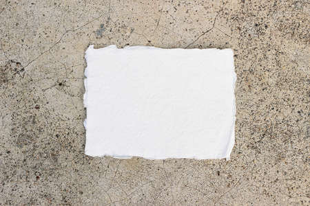Modern minimal stationery still life. Blank cotton paper greeting card , invitation mock up on grunge texture concrete background. Flat lay, top view. Empty copy space.