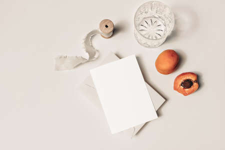 Summer wedding still life. Glass of water, cocktail, cut apricot fruit and silk ribbon on beige table background. Blank greeting card mock up scene. Flat lay, top view. Birthday party concept.