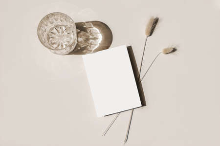 Modern summer stationery still life. Glass of water, cocktail, ong shadows and Lagurus ovatus grassy foliage. Blank greeting card mock up scene. Beige table background in sunlight. Flat lay, top view. Stock fotó
