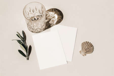 Summer still life. Glass of water, cocktail with long shadows, sea shellt and olive tree branch on beige table background in sunlight. Blank greeting card mockup. Flat lay, top view. Birthday concept.