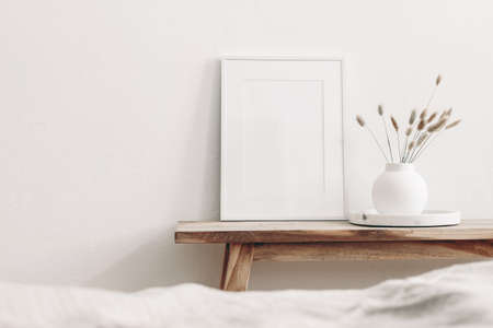 Portrait white frame mockup on vintage wooden bench, table. Modern white ceramic vase with dry Lagurus ovatus grass and marble tray. Blurred beige linen blanket in front. Scandinavian interior.