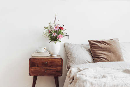 Cup of coffee and books on retro wooden bedside table. Rustic white ceramic vase with bouquet of pink cocmos and zinnia flowers. Beige linen and velvet pillows in bed. Scandinavian interior, bedroom. Stock fotó