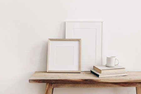 Wooden square and white portrait frame mockups on vintage bench, table. Cup of coffee on pile of books. White wall background. Scandinavian interior, neutral color palette. Artistic display concept.
