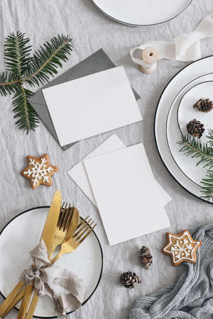 Christmas table setting. Blank greeting cards mockup scene. Golden cutlery, green fir tree branches. Plates and gingerbread cookies, linen table cloth. Holiday background. Vertical flat lay, top view