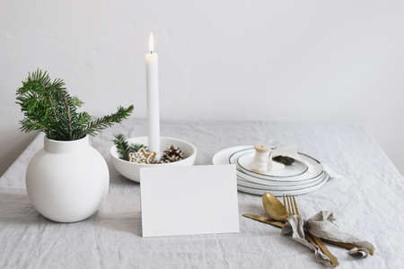 Traditional Christmas table place setting. Golden cutlery, fir tree branches in vase, plates and burning candle in ceramic candleholder on linen table cloth. Holidays background. Place card mockup Stock fotó