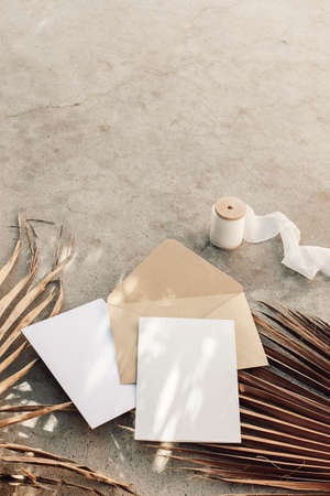 Summer boho wedding stationery still life. Blank greeting cards, envelope mock-ups and silk ribbon. Dry palm leaves on grunge concrete background. Flat lay, top view. Tropical vacation concept. Stock fotó