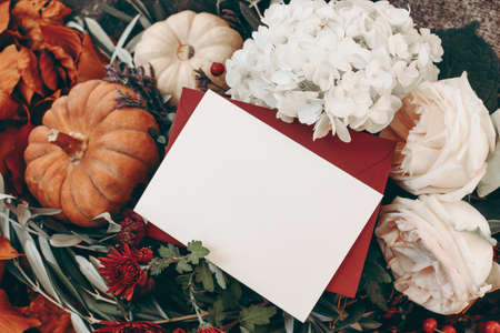 Autumn still life. Blank greeting card, envelope mock up. Mums, pink roses and hydrangea flowers. White and orange pumkins, live branches. Harvest, gardening concept. Thanksgiving, Halloween.