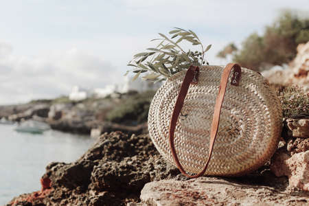 Summer vacation still life. French straw basket with olive tree branches on beach rocks. Blurred background with sea, white houses and boat. Selective focus. Mediterranean Mallorca island travel. Stock fotó