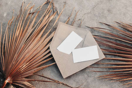Summer stationery still life. Two blank business card mock-ups on craft envelope,dry palm leaves. Grunge beige concrete textured background. Flat lay, top view. Tropical vacation concept. Moody boho