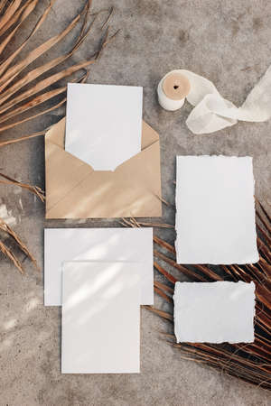 Tropical wedding invitation suite. Summer stationery mock-up scene. Blank greeting cards with dry palm leaves in sunlight. Shadow overlay. Grunge concrete background. Vertical flat lay, top view.