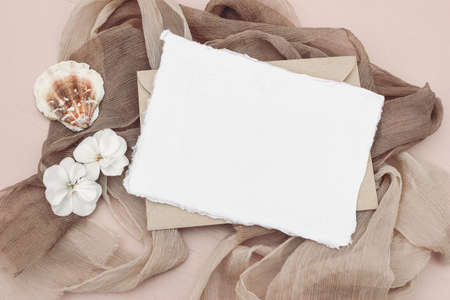 Summer stationery still life scene. Blank greeting card mock-up and craft envelope. Beige silk scarves, white flowers and sea shell. Flat lay, top view. Feminine lifestyle and vacation concept.