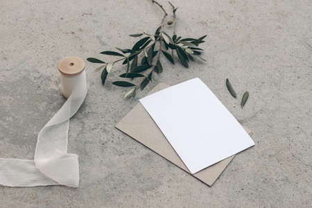 Summer wedding stationery or birthday mock-up scene. Blank greeting card, envelope, silk ribbon and olive branches and fruit. Grunge concrete background. High angle view. Mediterranean design.