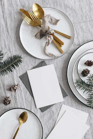 Christmas table setting. Festive greeting cards mockup scene. Golden cutlery, green fir tree branches. Plates and pine cones, linen table cloth. Holiday background. Vertical flat lay, top view