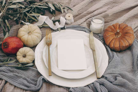 Autumn table setting with golden cutlery, olive branches and porcelain plate. Pumpkins and pomegranate fruit. Blank menu card mockup. Fall, Thanksgiving and Rosh Hashanah celebration concept.