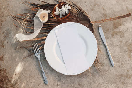 Summer setting with cutlery, dry palm leaf and porcelain plate. Coconut, silk ribbon and white oleander flowers on grunge concrete background. Blank menu card mockup. Tropical wedding concept. Stock fotó