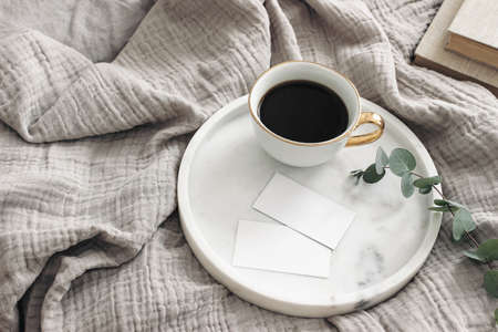 Breakfast in bed stationery mockup scene. Cup of coffee, blank business cards on white marble tray. Green eucalyptus tree branch and books on muslin throw. Lifestyle concept. High angle view. Stock fotó