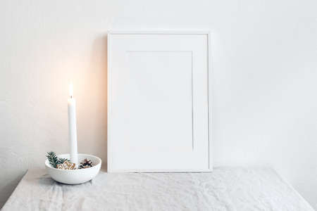 White picture frame mockup scene. Christmas seasonal still life. Burning candle in ceramic candle holder. Scandinavian interior. Gingerbread stars cookies and fir tree branches. White wall background.