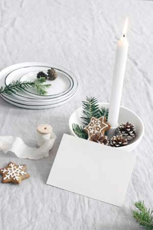 Christmas still life composition. Blank greeting, place card mockup. Gingerbread stars cookies and fir tree branches. Burning candle in white ceramic candle holder. Seasonal photo. Scandinavian design