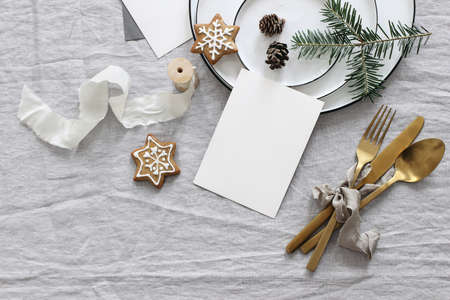 Plates, pine cones on table cloth. Winter festive greeting cards mockup scene. Golden cutlery,gingerbread cookies and fir tree branches. Christmas table setting. Holiday background. Flat lay, top view
