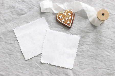 Christmas textile mockup scene. White cotton fabrics swatches on linen table cloth background. Gingerbread heart cookie, decorative sugar frosting and silk ribbon. Winter holiday flat lay, top view.