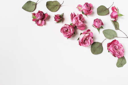 Feminine wedding desktop composition with pink roses flowers, dry green eucalyptus leaves isolated on white table background. Floral pattern. Empty space. Flat lay, top view. Picture for blog. Stock fotó