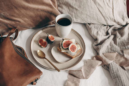 Fall breakfast still life. Bread sandwich with cheese and skiced fig, leather bag and cup of coffee on white linen background. Velvet and linen pillows in bed. Thanksgiving, autumn concept. Top view. Stock fotó