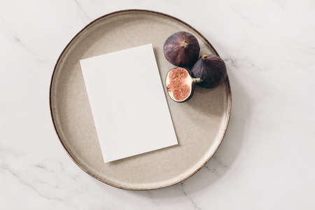 Autumn still life. Blank greeting card mockup, cut figs fruit and ceramic plate on white marble table background. Fall and Thanksgiving concept. Styled stock flat lay photography. Top view.