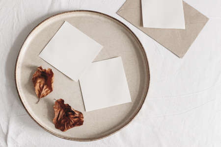 Autumn composition. Blank memo cards mockups, craft envelope and dry beech leaves on white linen table cloth background. Fall and Thanksgiving concept. Styled flat lay photography. Top view. Stock fotó