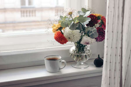 Feminine autumn still life. Cup of coffee, bouquet of colorful dahlia flowers in glass vase on windowsill. Styled moody floral composition with fig fruit. Window with white curtain. Selective focus.