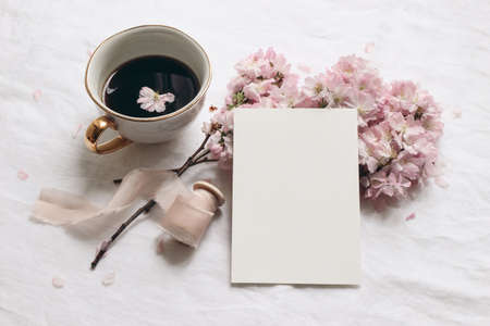 Wedding stationery mock-up. Blank greeting card and cup of coffee. White linen tablecloth background. Pink blossoming cherry tree branches and ribbon. Feminine still life composition. Flat lay,top.
