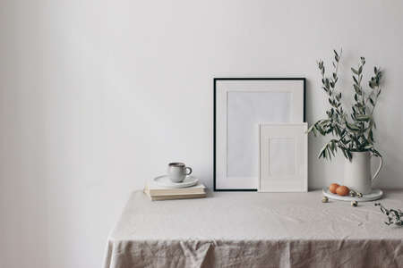 Spring, Easter breakfast still life. Cup of coffee, books and empty picture frames mockups. Linen tablecloth. Olive tree branches in ceramic jug. Hen, quail eggs. Farmhouse, Scandinavian interior. Stock Photo