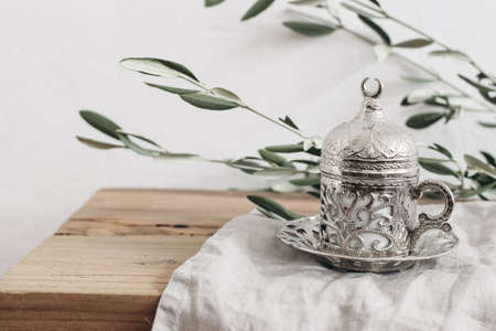 Ramadan Kareem greeting card, invitation. Closeup of ornamental decorative silver cup and saucer with tea or coffee. Blurred green olive tree branches. Old wooden table background. Muslim Iftar dinner