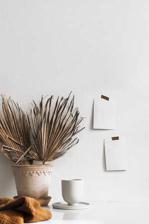 Summer breakfast still life. Cup of coffee and dry palm leaves in flower pot on table. Empty notepads and posters mockups taped on white wall. Boho tropical working space, home office. Vertical. Stock Photo