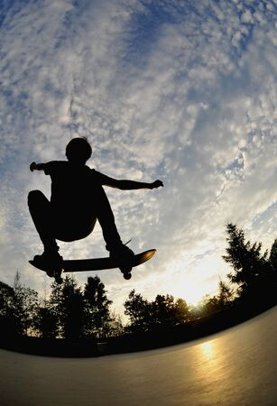 boy skater: silhouette of a skateboarder in action  Stock Photo