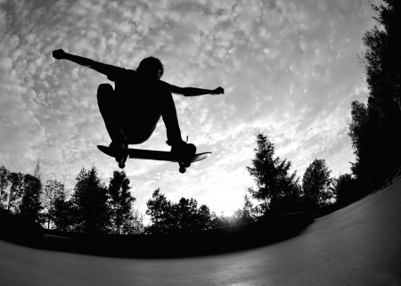 youth culture: silhouette of a skateboarder in action  Stock Photo