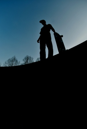 halfpipe: silhouette of a skateboarder standing on top of a massive skateboard ramp